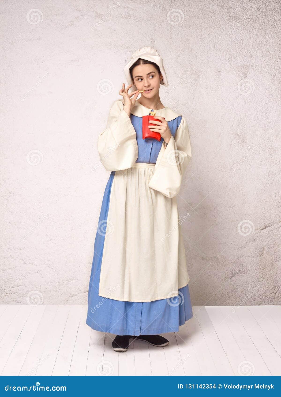 Mittelalterliche Frau in historisches Kostüm-tragendem Korsett-Kleid und Mütze