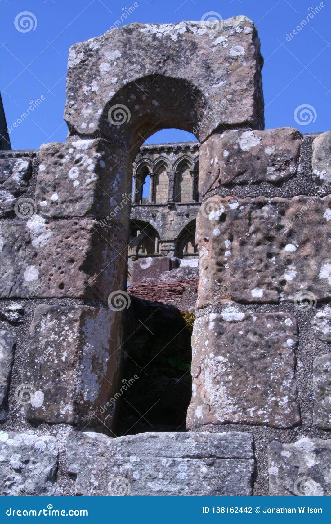 Mittelalterliche Ruinen angesehen durch ein Steinbogenfenster