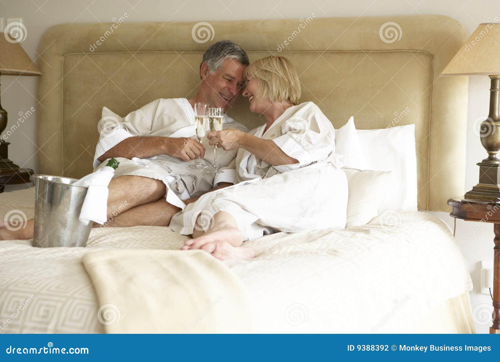 Mittlere gealterte Paare, die Champagne im Schlafzimmer genießen