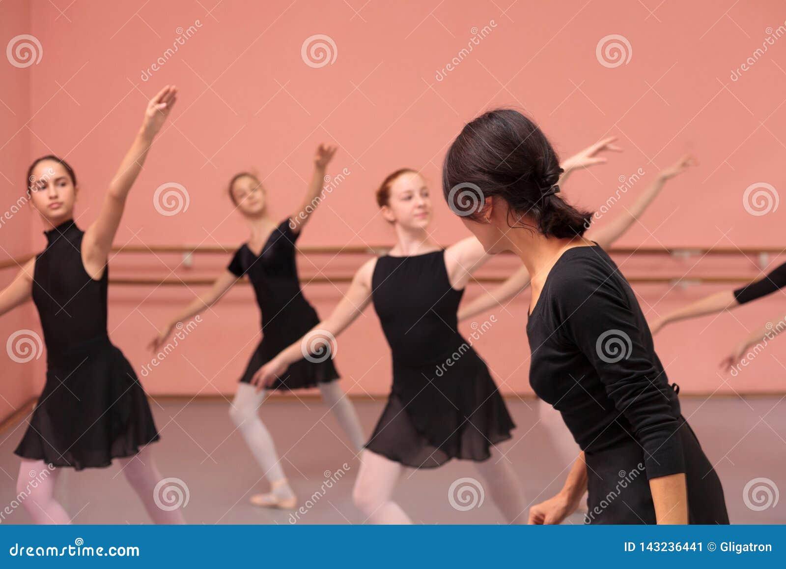 Mittlerer erwachsener weiblicher Ballettlehrer, der mittlere Gruppe Jugendlichen anweist