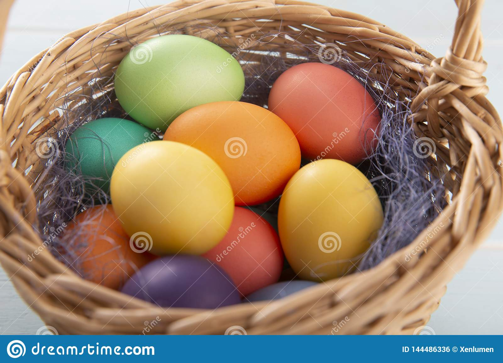 Mix of dyed bright Easter eggs in a withe basket with colorful blue sisal