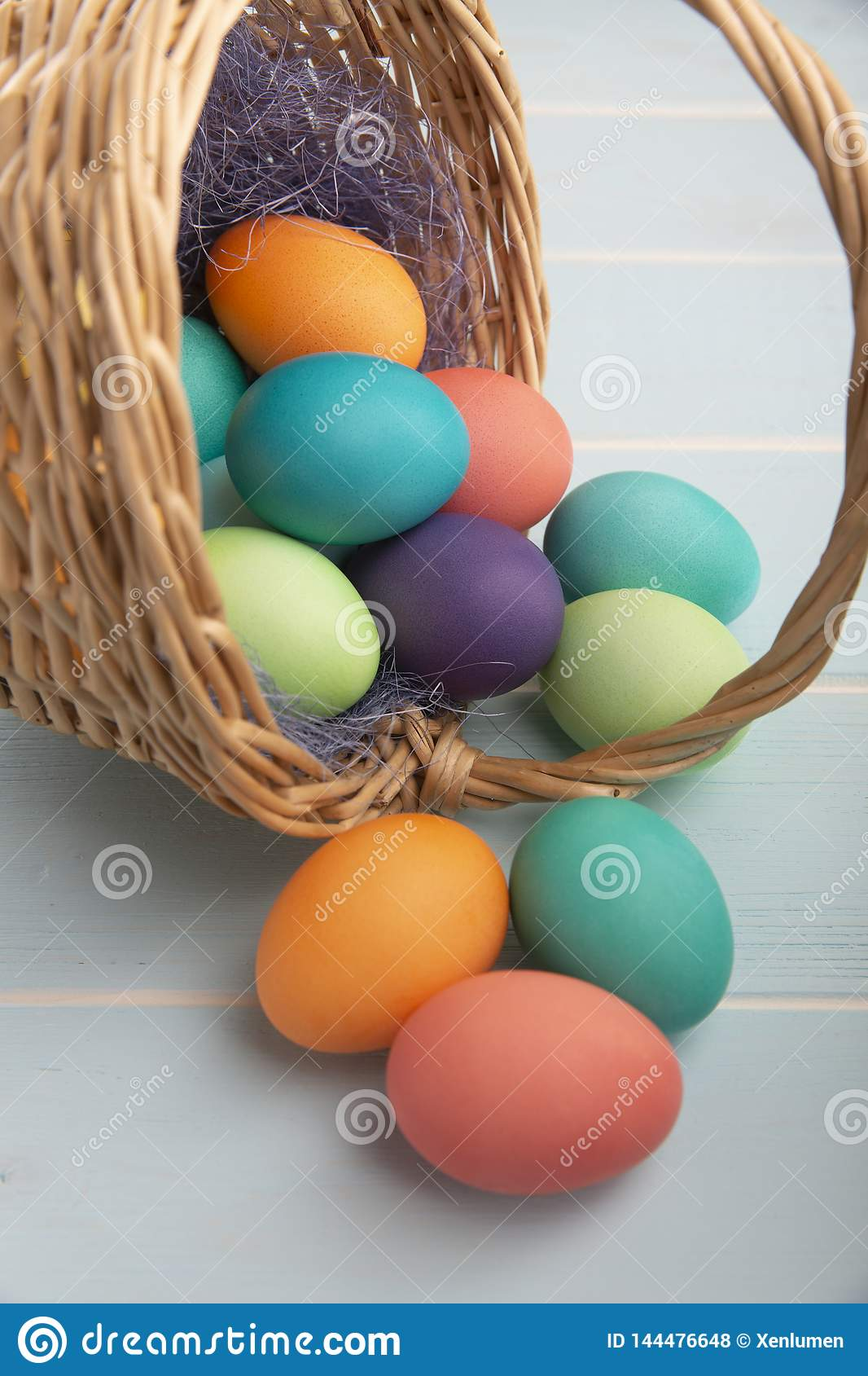 Mix of dyed bright Easter eggs in a withe basket with colorful blue sisal  on a wooden blue surface