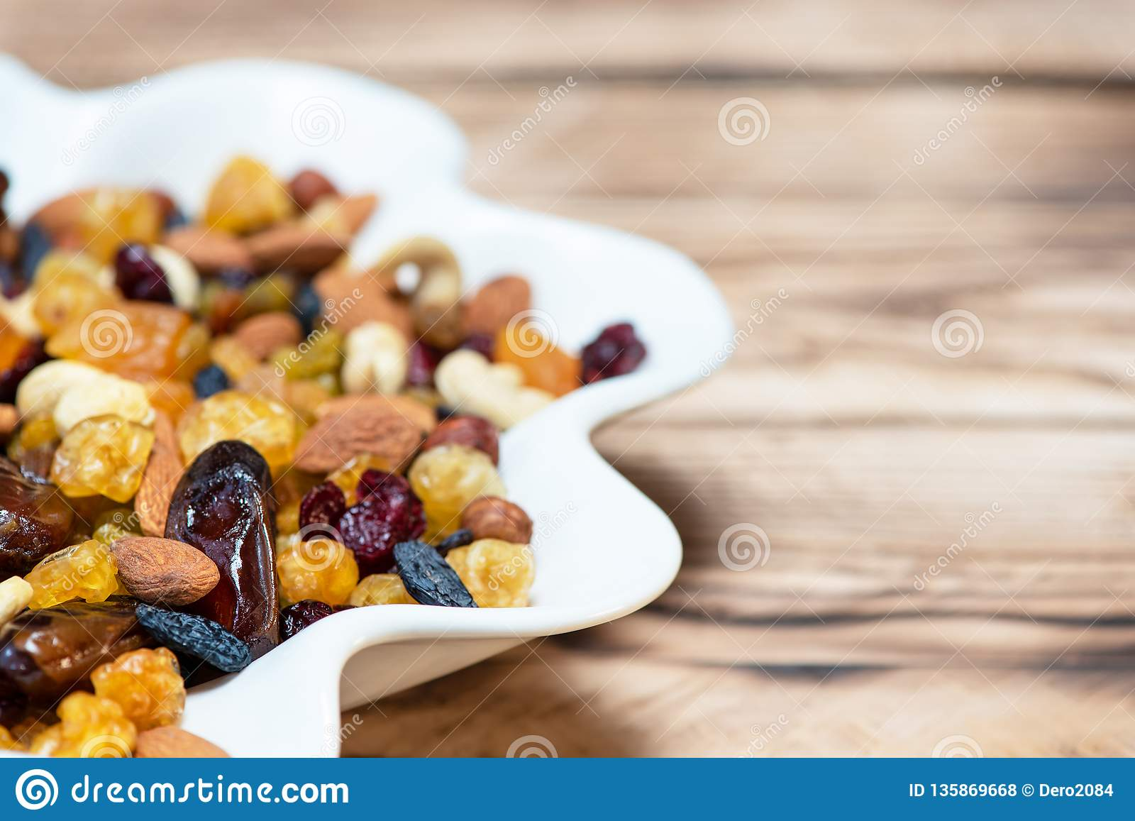 Mix of nuts and berries. Dried fruits in white plate on wooden table, copy space for text. Healthy food and vitamins