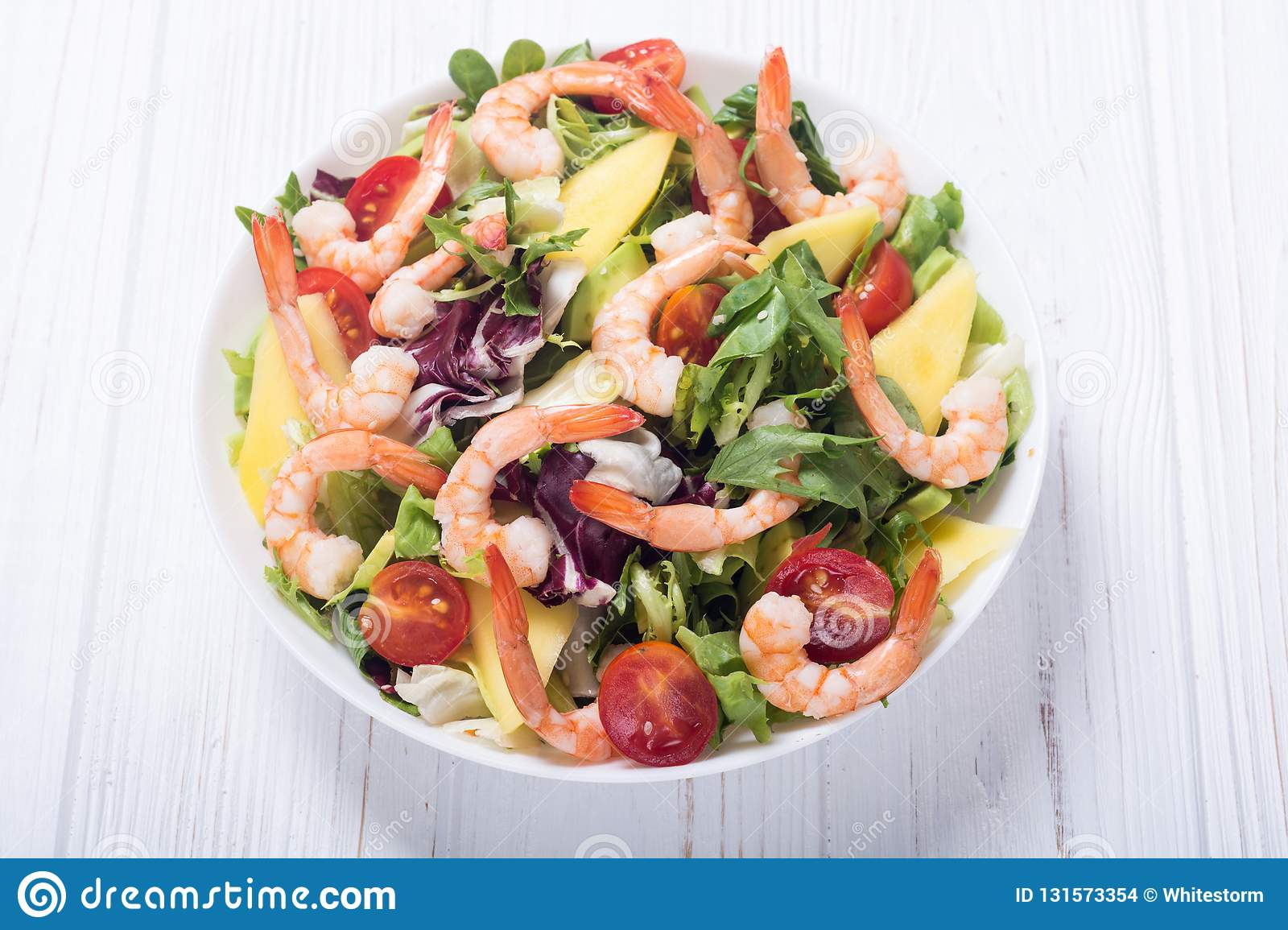 Mix of salad with shrimps avocado and cherry tomatoes . Healthy food background