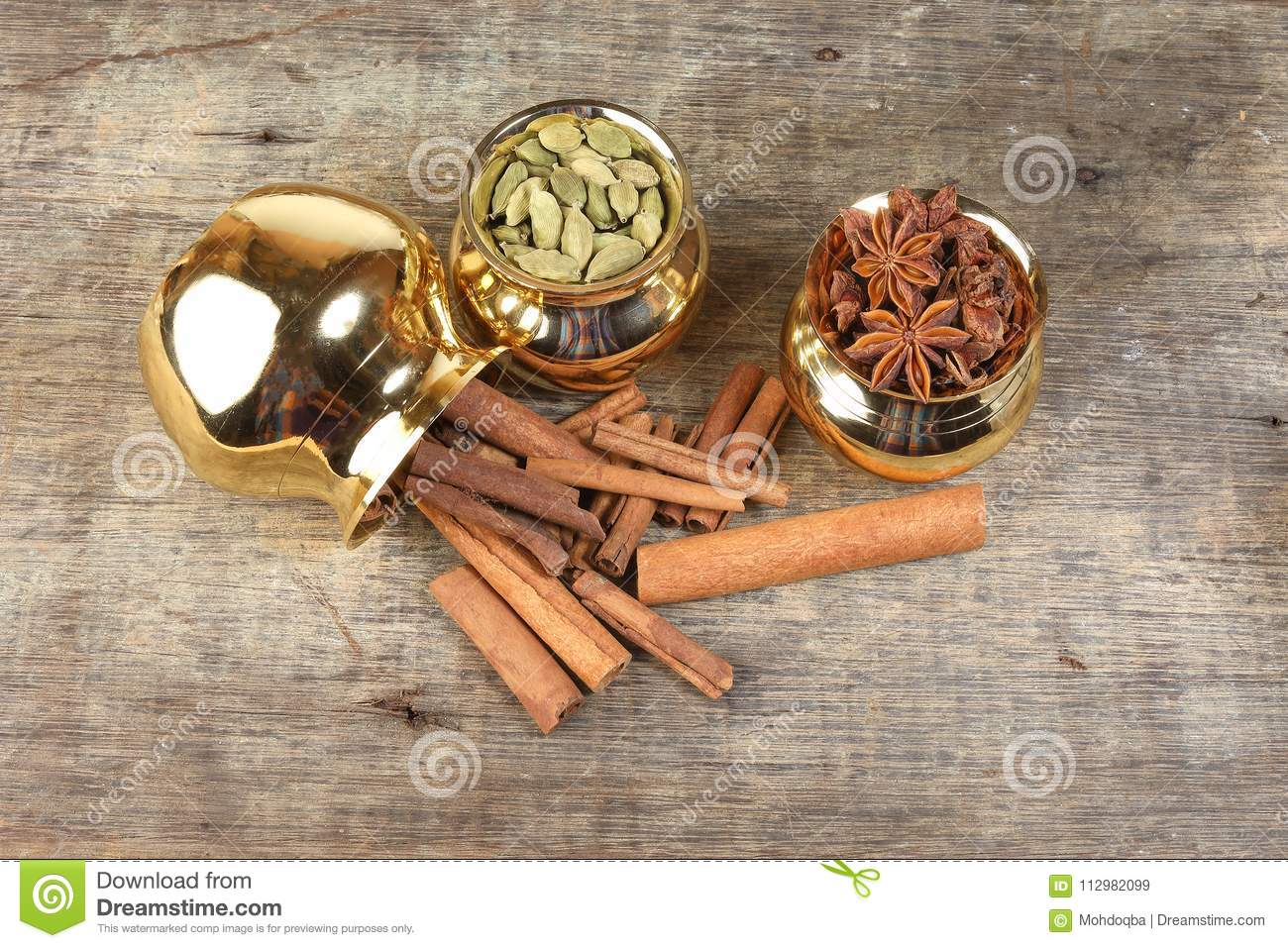 Mix spice in golden metal pot on rustic wood