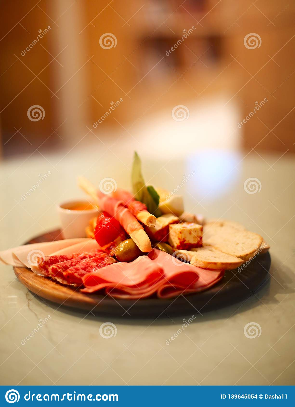 Mix of traditional spanish ham salami, parma ham on grissini bread sticks, marinated vegetables and olives on wooden plate with
