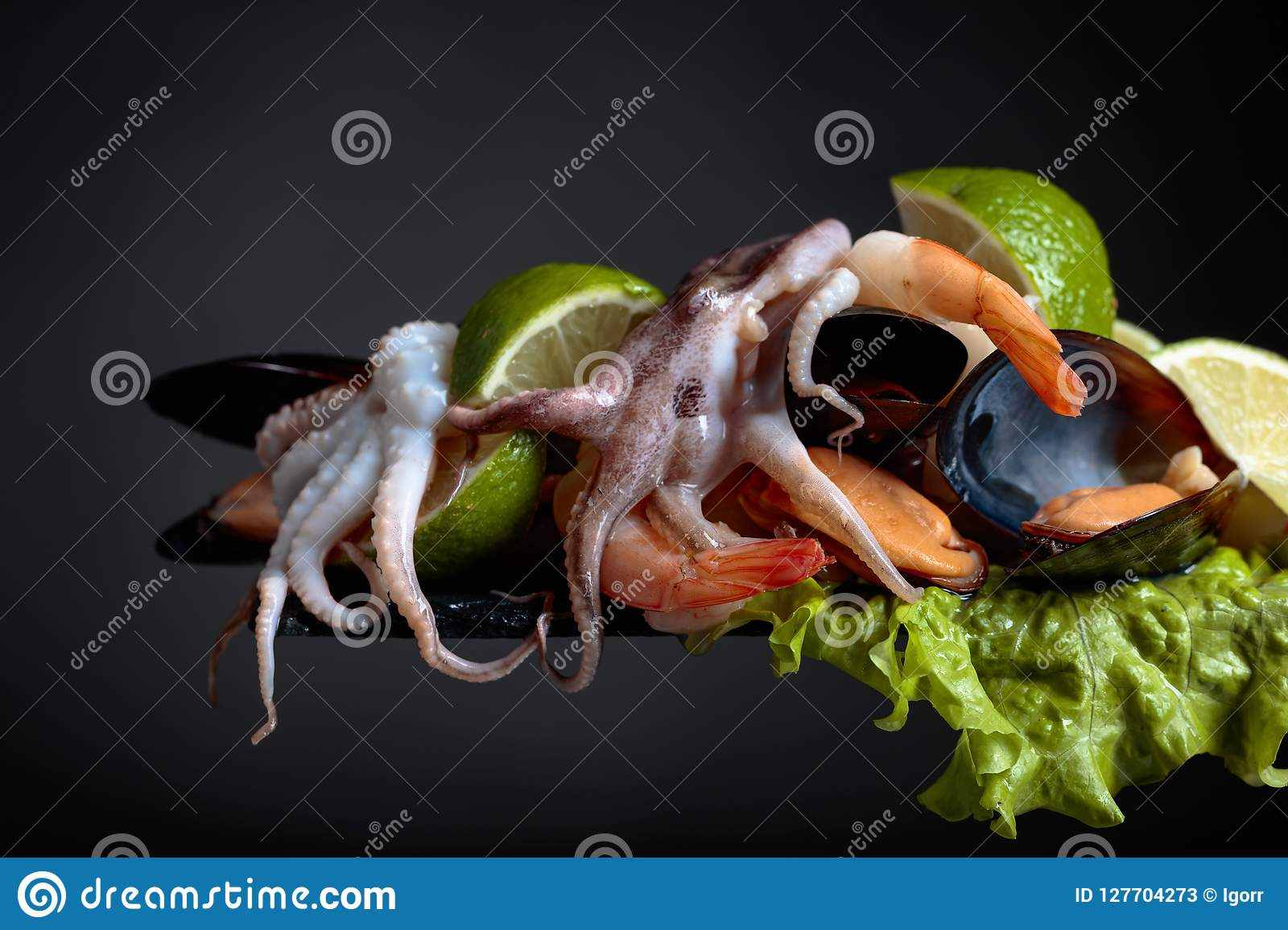 Mixed delicious seafood with salad and lime slices .