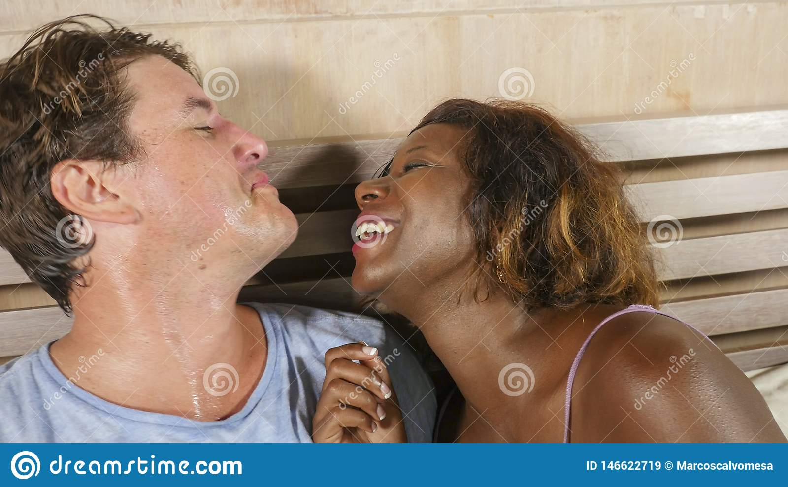 Mixed ethnicity couple in love cuddling together at home in bed with beautiful playful black afro American girlfriend or wife and