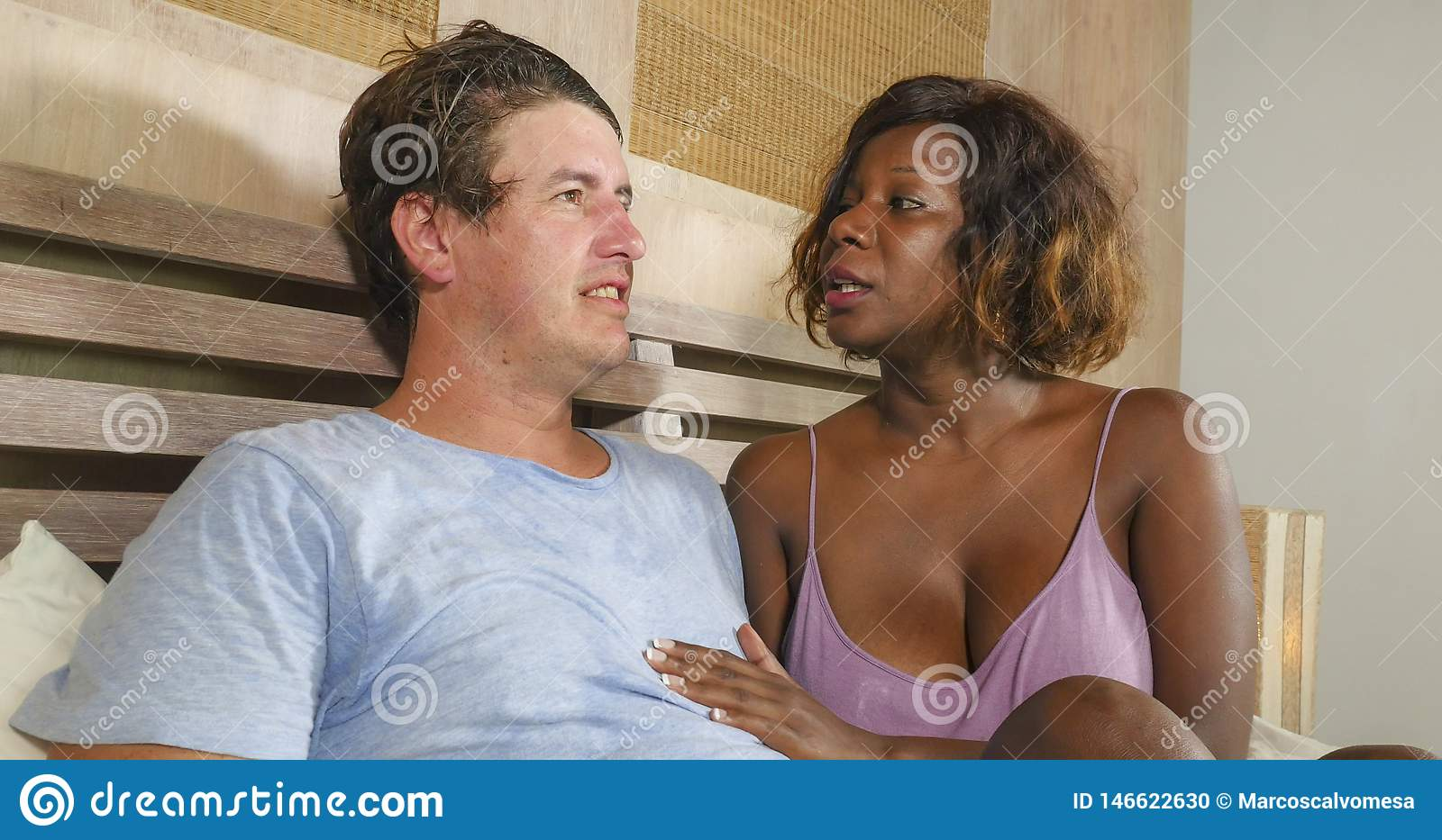 Mixed ethnicity couple in love cuddling together at home in bed with beautiful playful black afro American woman and white