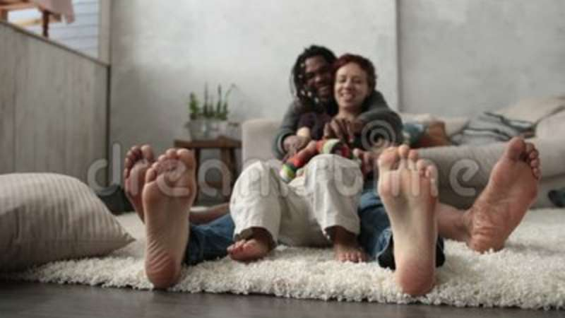 mixed family with son sitting barefoot on floor stock footage