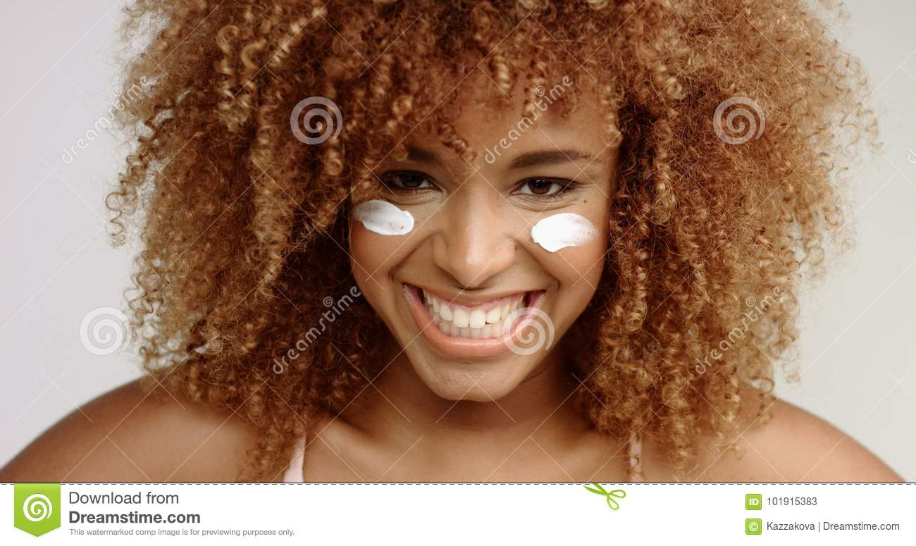 Mixed Race Black Woman With Blonde Curly Hair In Studio With Cream