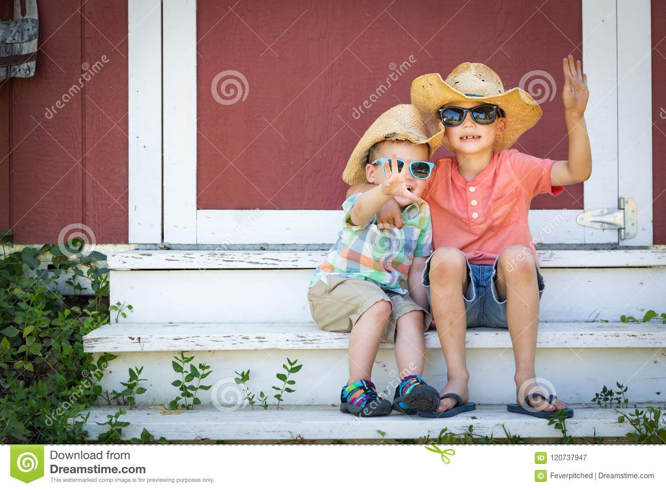 Mixed Race Chinese and Caucasian Young Brothers Having Fun Wearing Sunglasses and Cowboy Hats