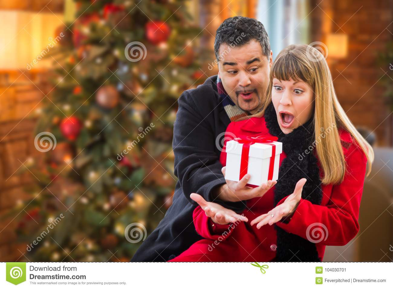 Ecstatic Mixed Race Couple Sharing Christmas In Front of Decorated Tree.
