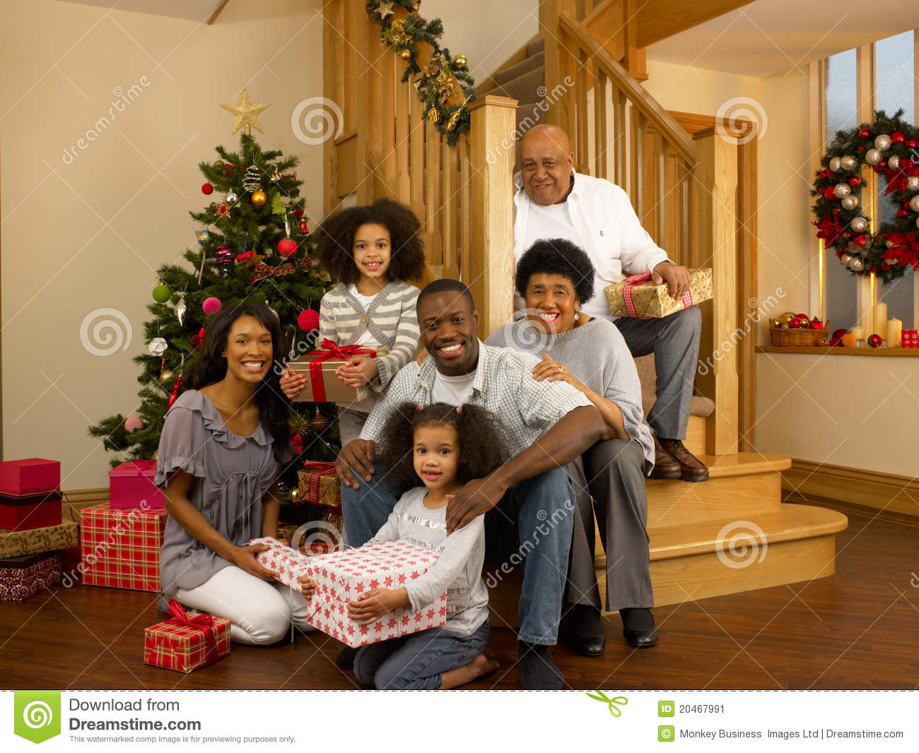 Mixed Race Family With Christmas Tree And Gifts Stock