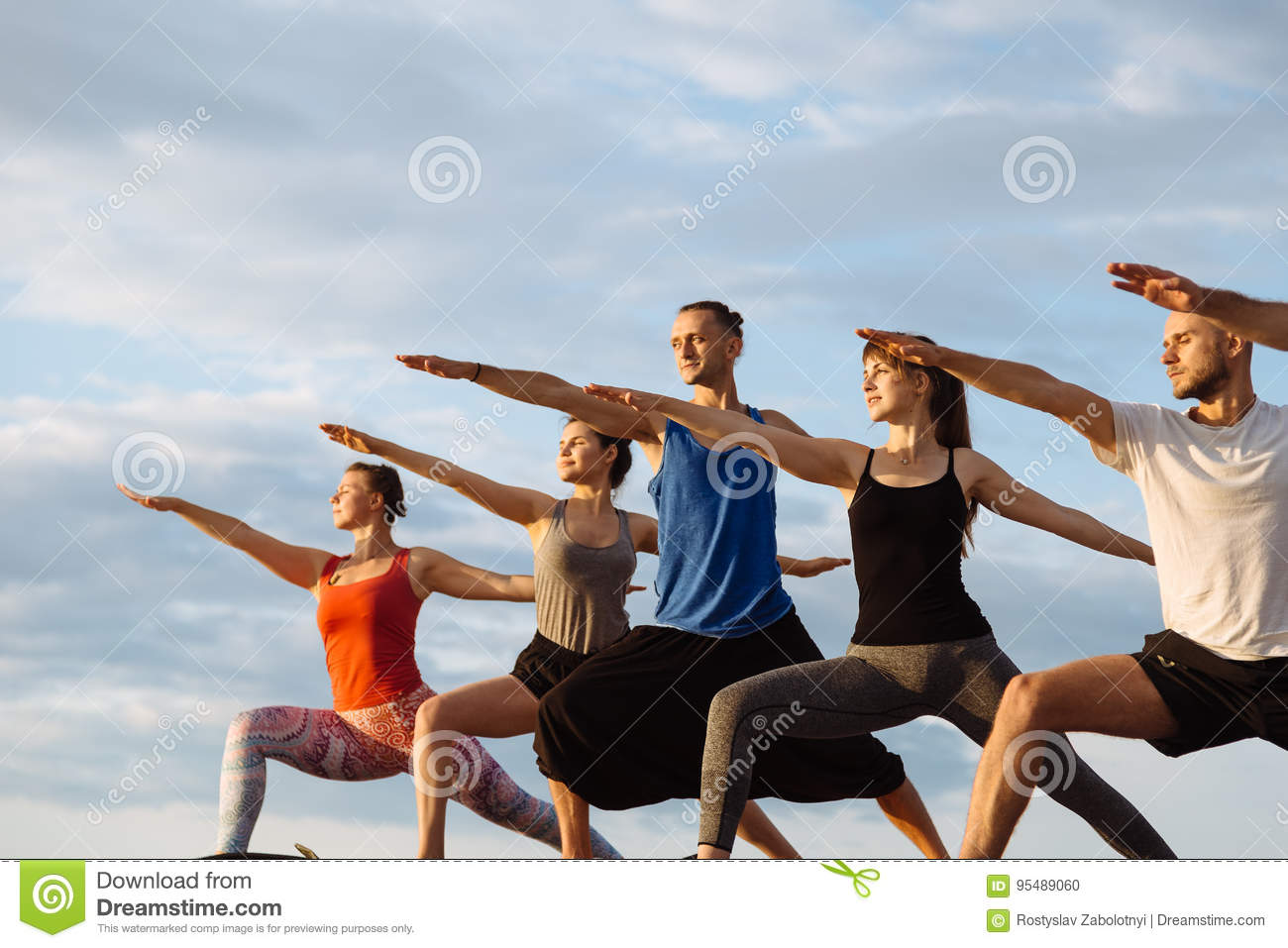 Mixed race group of people exercising yoga healthy lifestyle fitness warrior poses