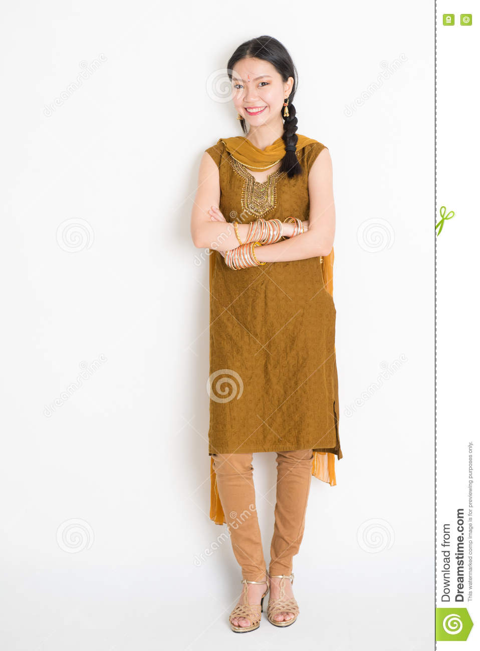 9419f7aa84 Portrait of young mixed race Indian Chinese female in traditional punjabi  dress smiling, full length standing on plain white background.
