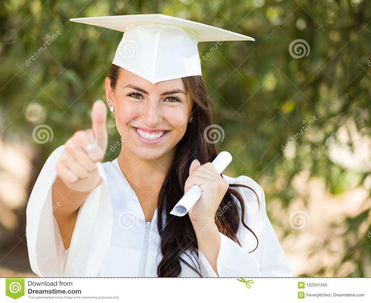 Mixed Race Teen Girl Gives Thumbs Up at Graduation In Cap and Gown