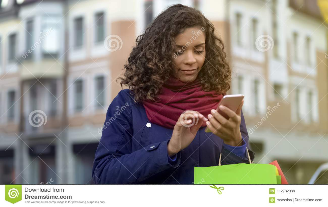 Mixed race woman checking online store apps on modern smartphone, shopping
