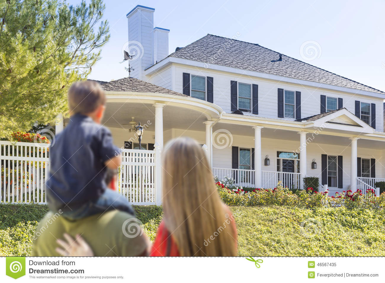 Mixed race young family looking at beautiful home stock for Beautiful new house