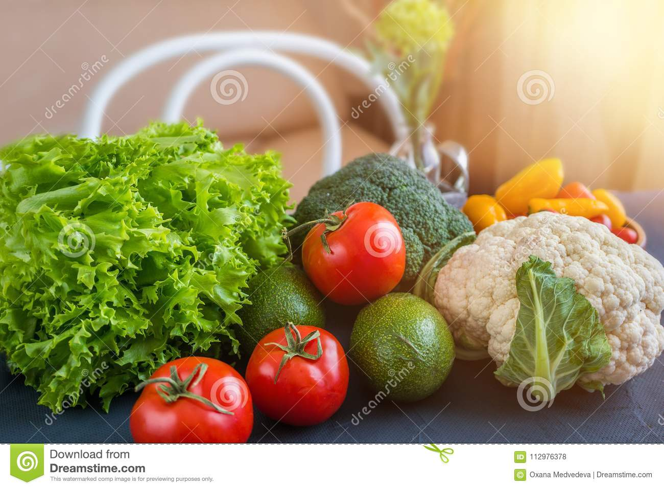 Mixed vegetables of cauliflower and broccoli, garlic, green onions, tomatoes and green peas on a wooden table in the kitchen to pr