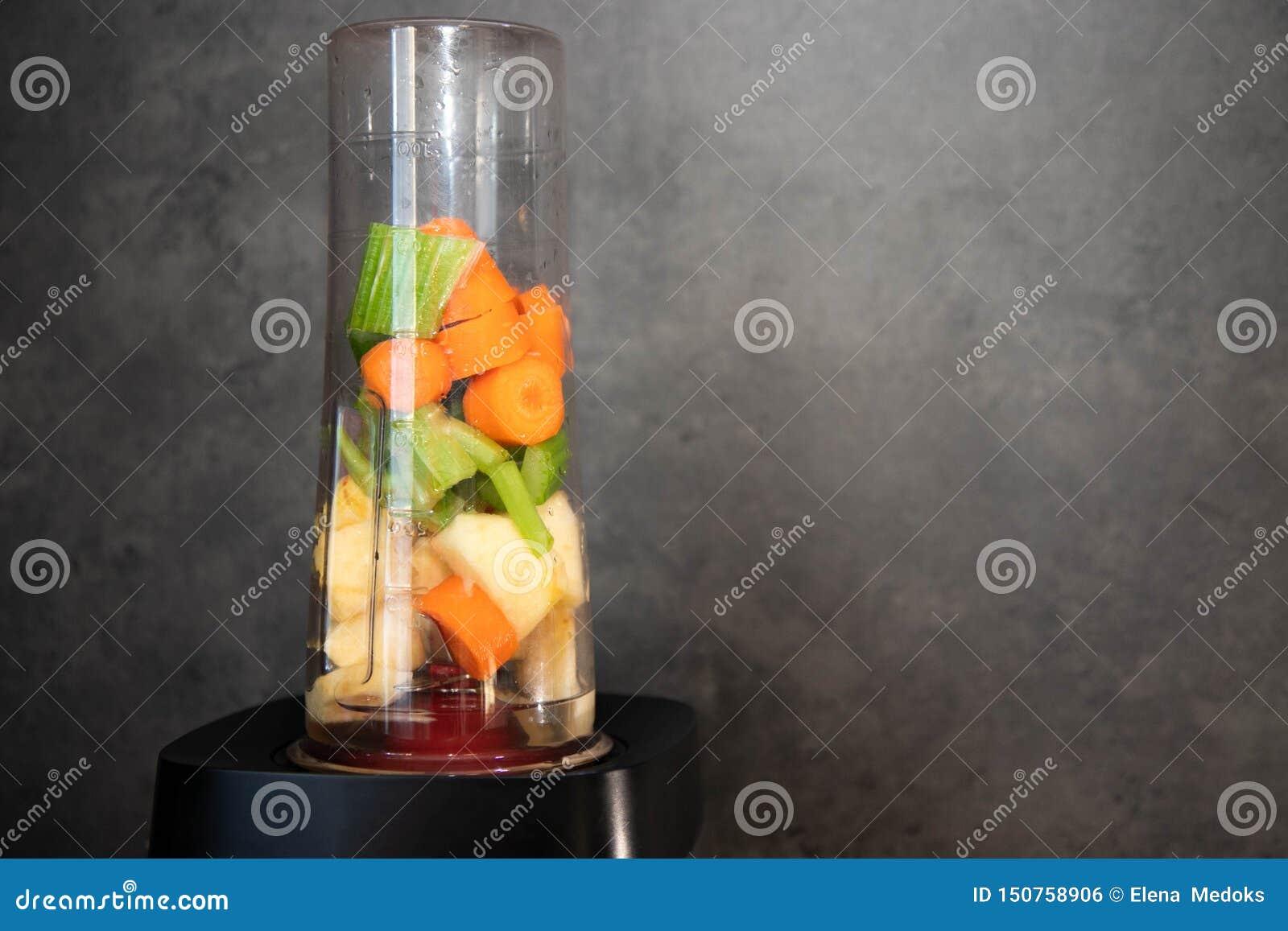 Mixer met Verse Groenten Gesneden selderie, appel en wortel in een mixerkop voor een smoothie Gezond voedsel De ruimte van het ex