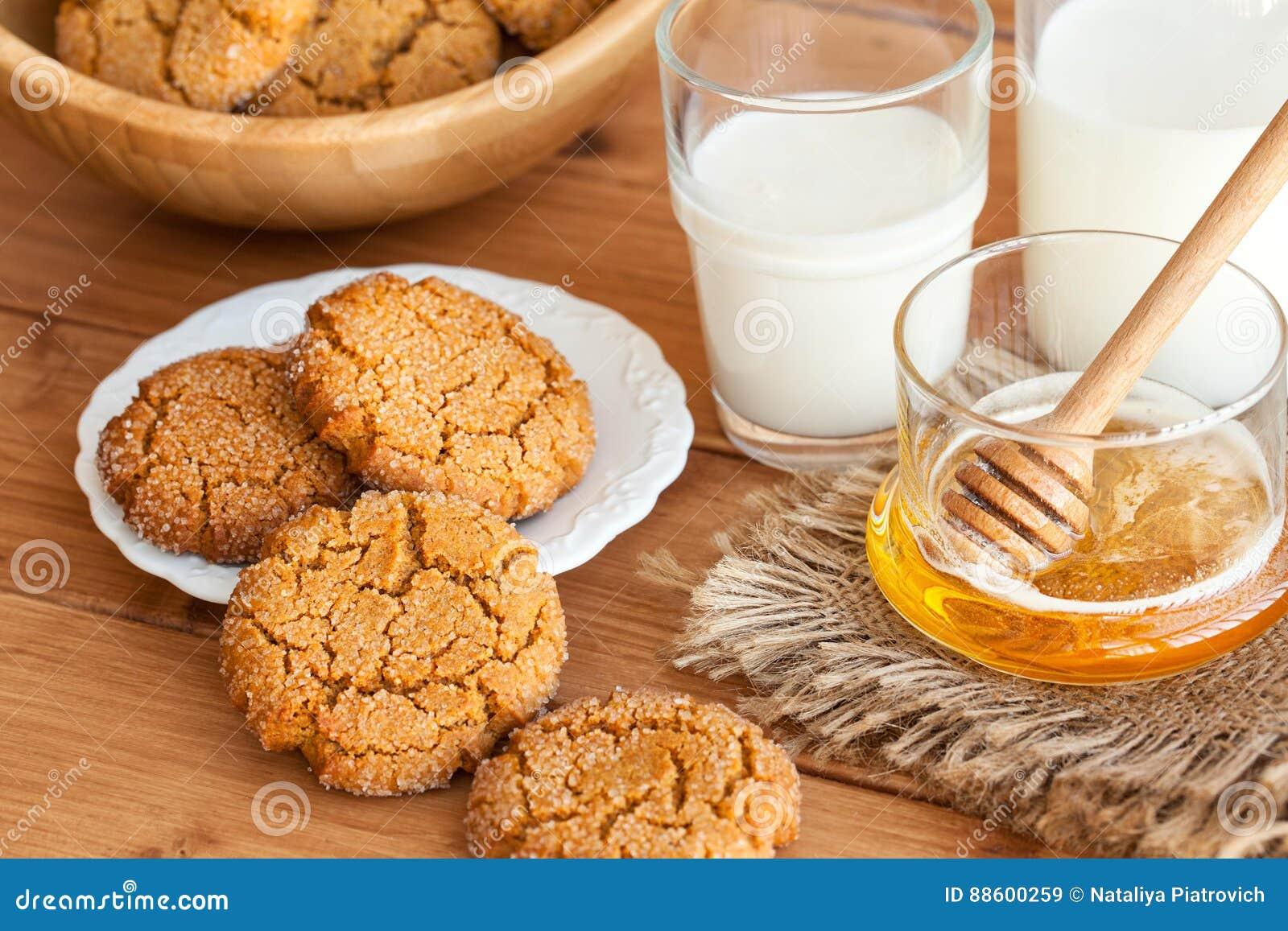 Mjölkar ljust rödbrun kakor för honung med på en lantlig bakgrund