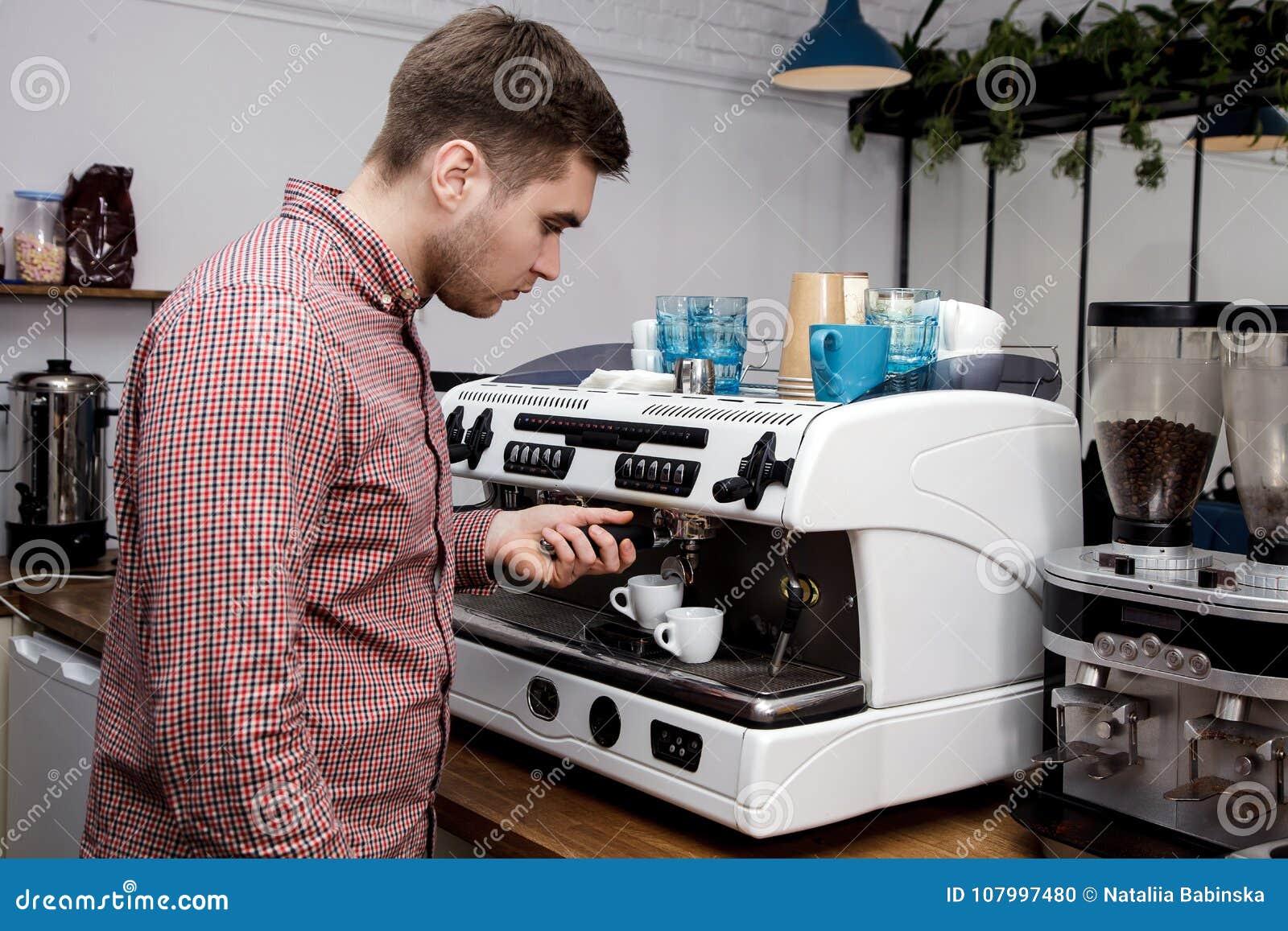 Mjölkar varm ånga för unga stiliga för baristahipsterdanande för kaffe för kafét för mannen korn för maskinen cappuccino för latt