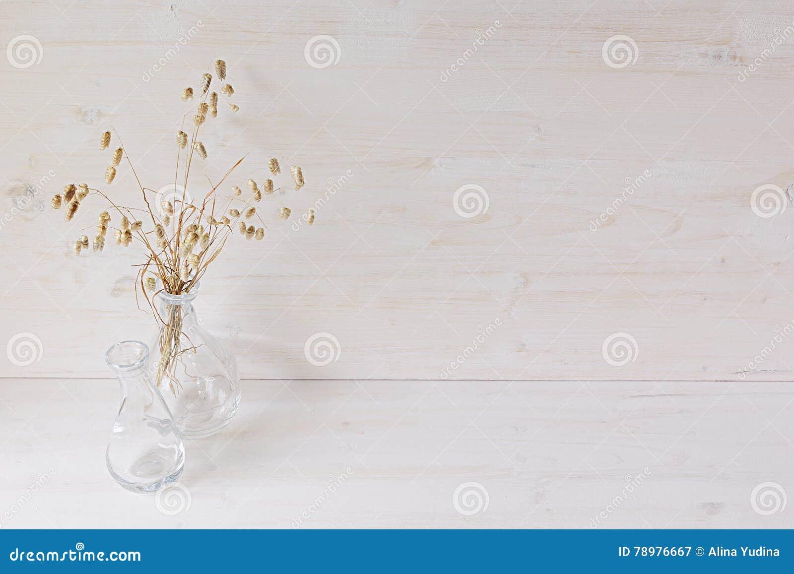 Mjuk hem- dekor av den glass vasen med spikelets på vit wood bakgrund