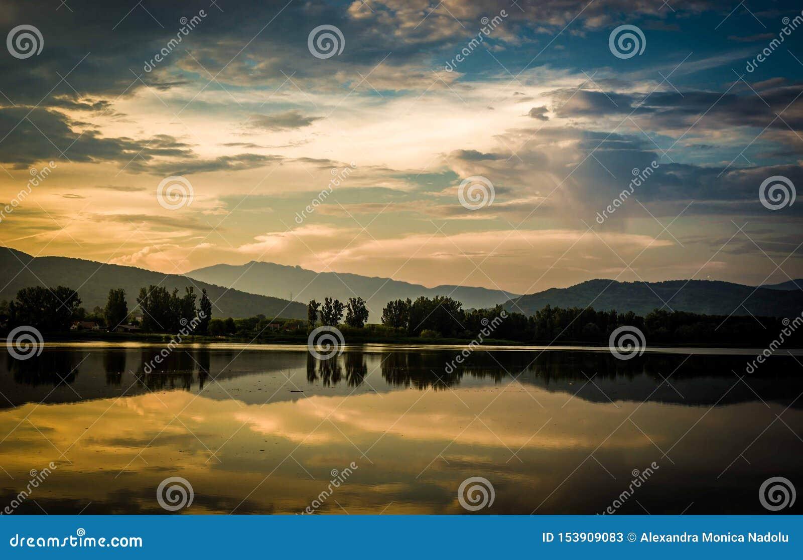 Mjuk utbredd färgglad solnedgång i skuggor av apelsinen som är blåa och som är purpurfärgade i molnig himmel över