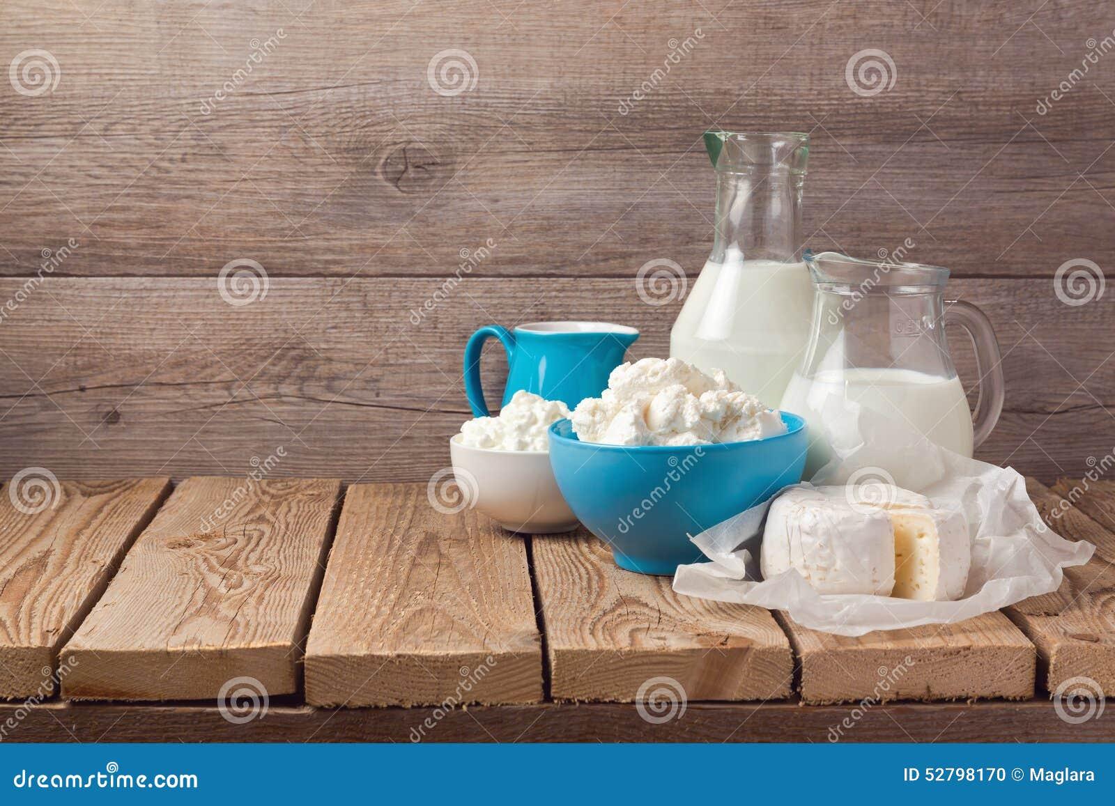 Mleka i chałupy ser nad drewnianym nieociosanym tłem