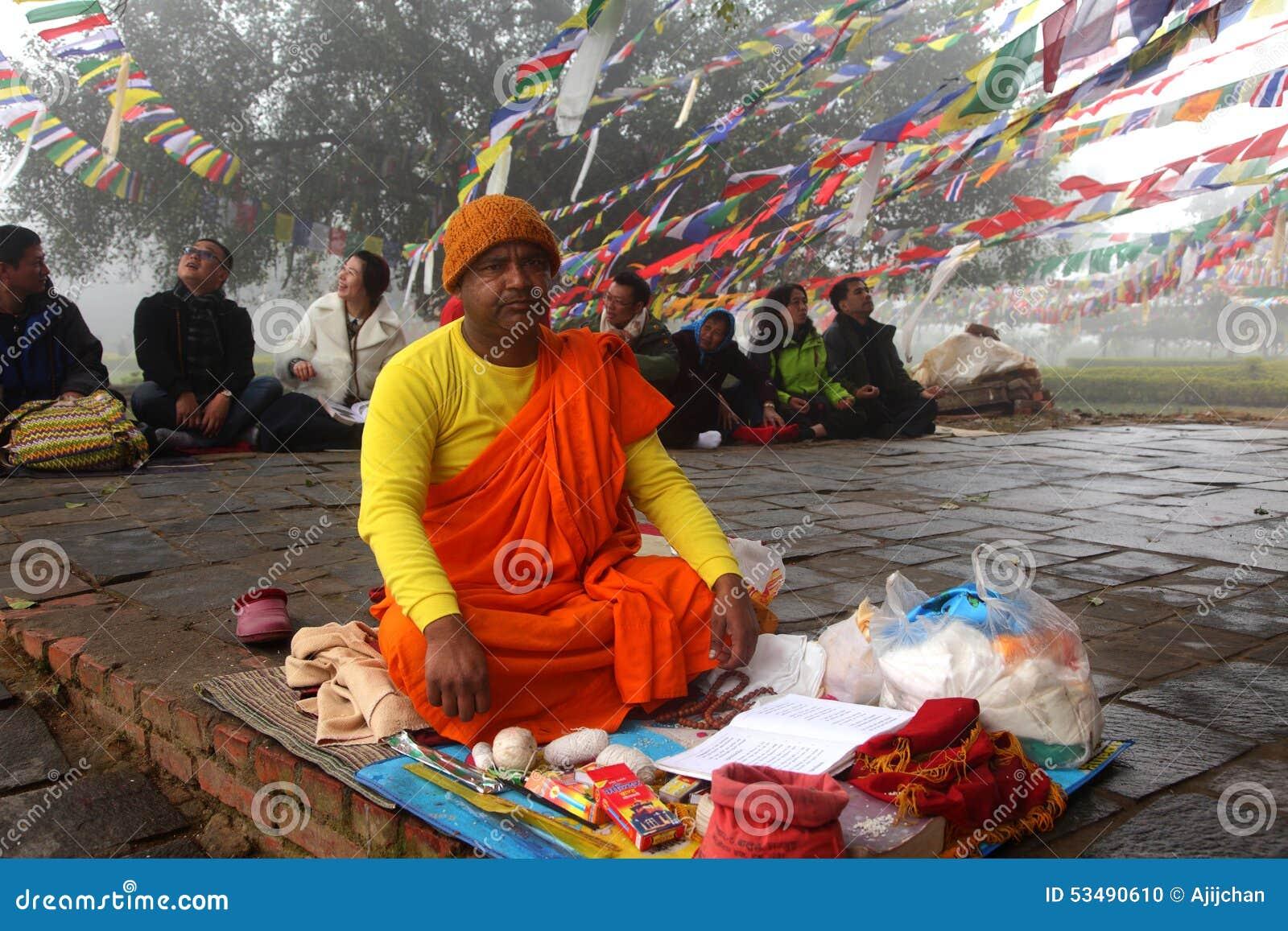 Mnich buddyjski robi religijnym rytuałom przed Mayadevi świątynią