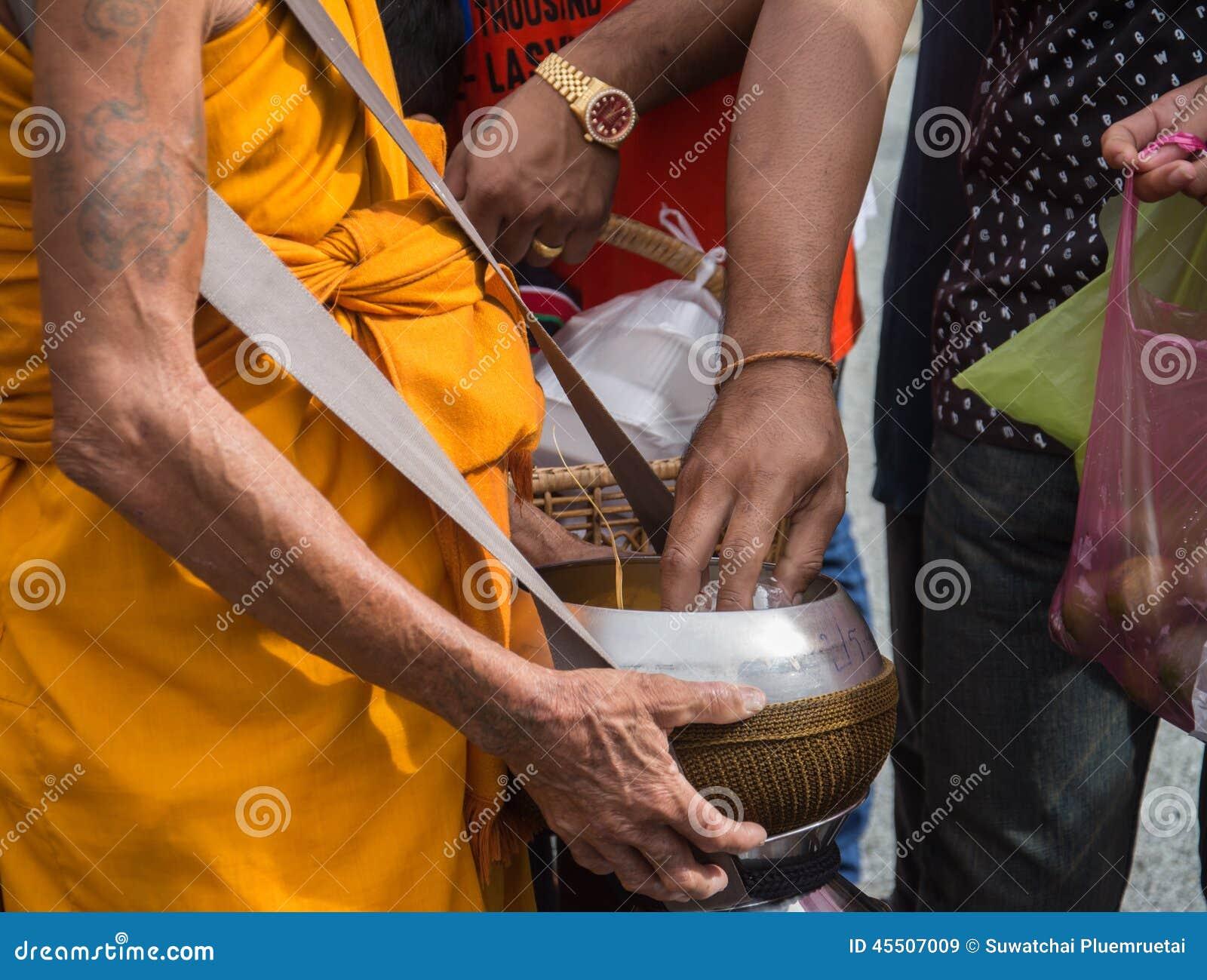 Mnichom buddyjskim dają karmowej ofiarze od ludzi
