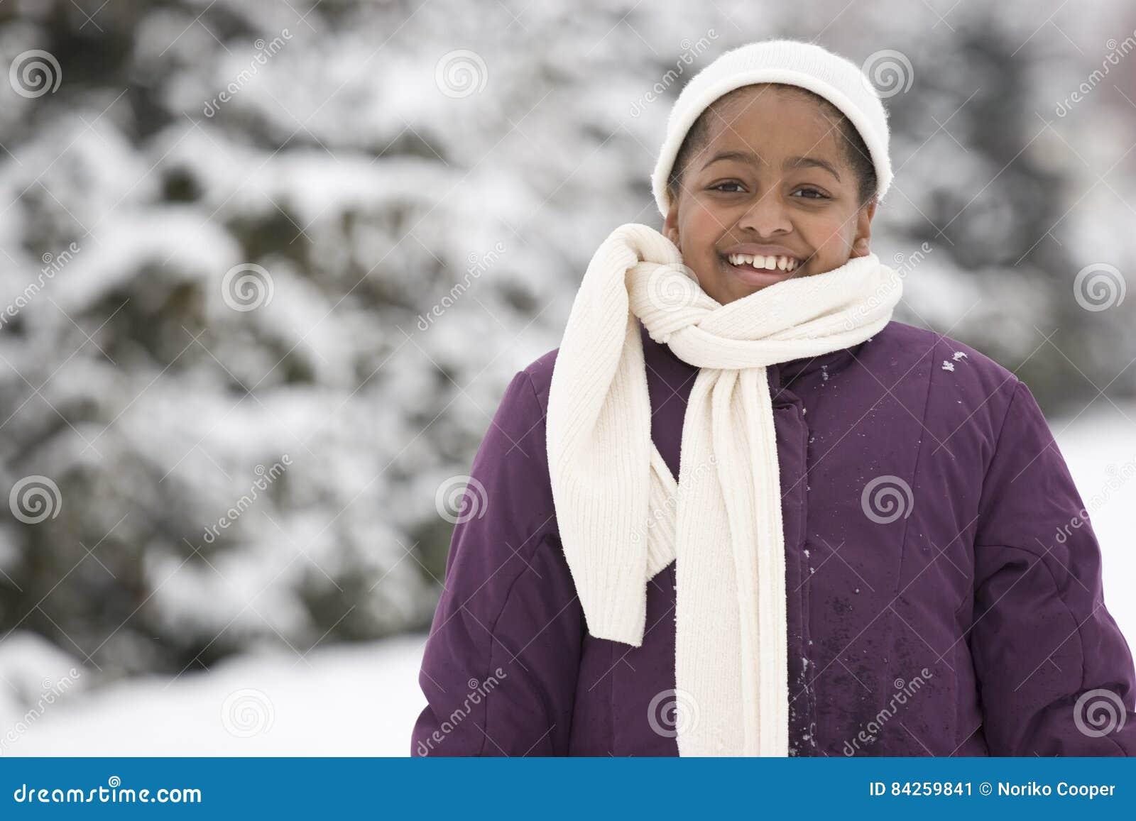 Moça afro-americano que sorri na neve