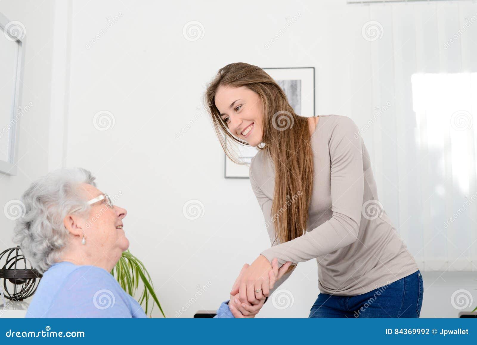 Moça alegre que toma da mulher superior idosa em sua casa