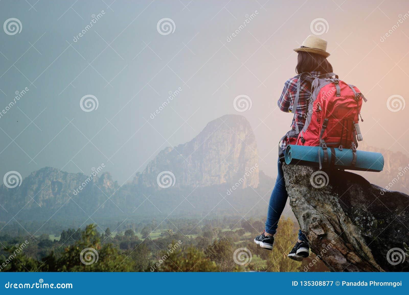 Moça asiática do moderno com trouxa que aprecia o por do sol na montanha máxima Conceito da aventura do estilo de vida do curso