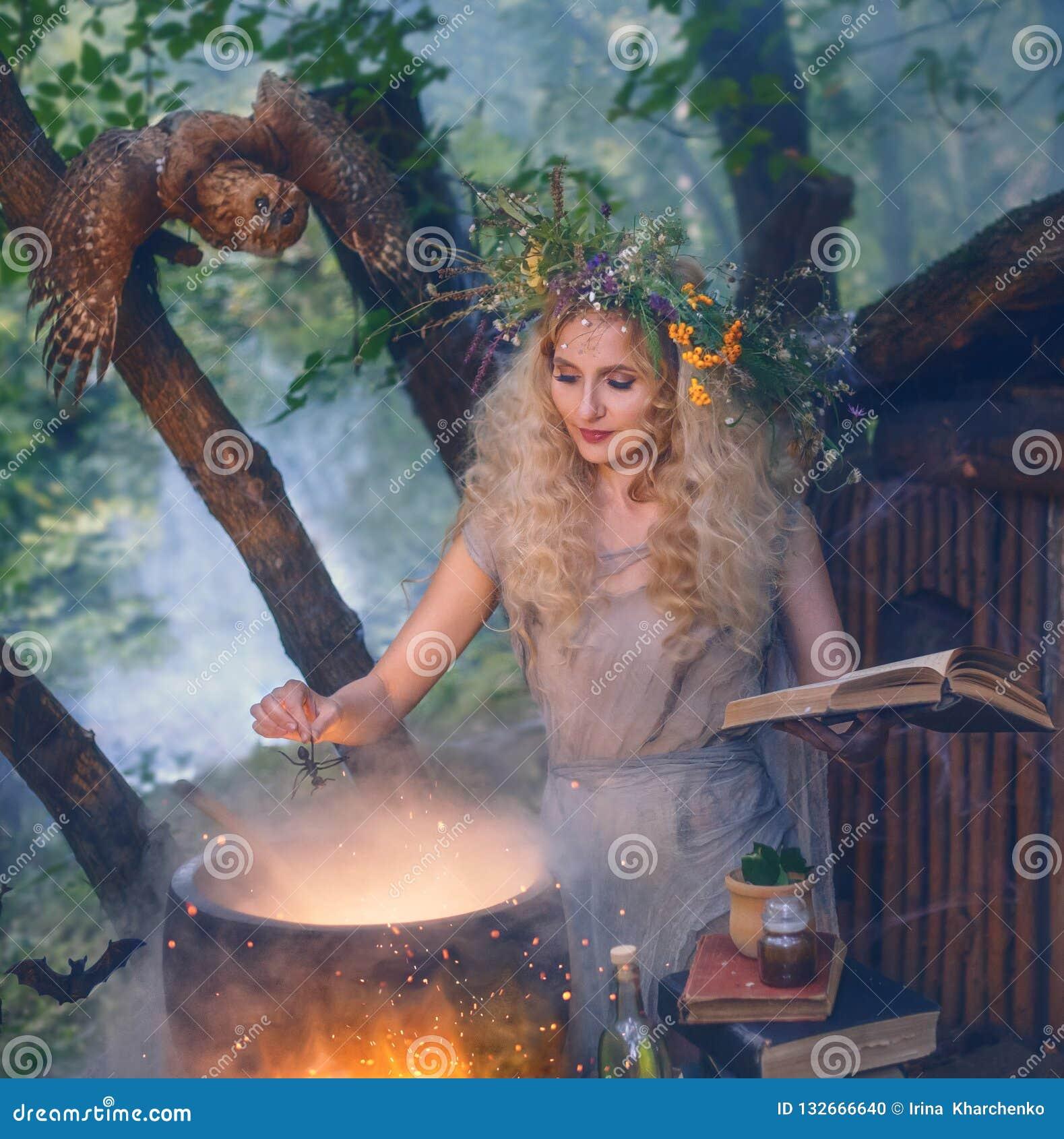Moça atrativa com cabelo louro com uma grinalda luxúria surpreendente em sua cabeça na floresta, preparando a poção no cauldro