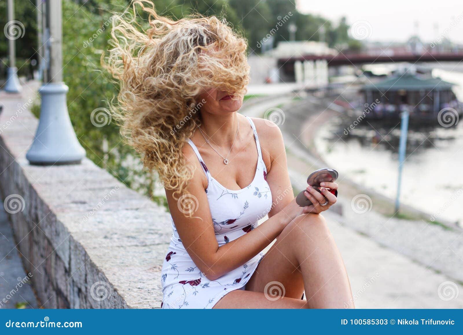 Moça atrativa com o cabelo louro encaracolado que tenta fixar seu M