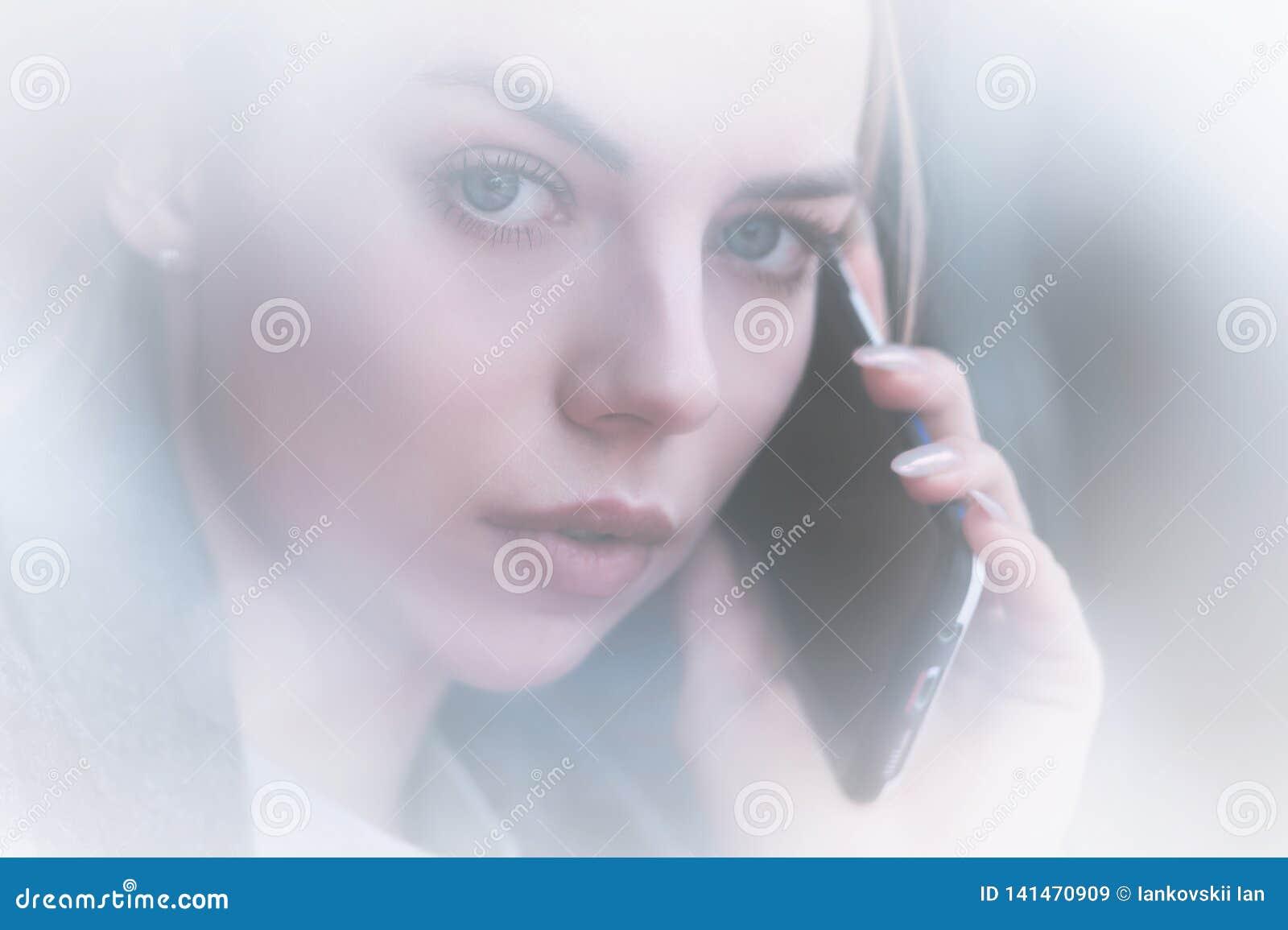 Moça atrativa do retrato do close up que fala no olhar do telefone na câmera opinião do Não-contraste com a reflexão de