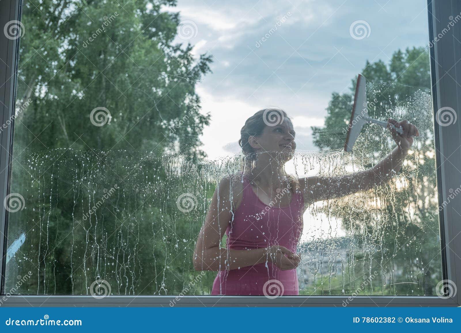 A moça bonita lava uma janela em uma casa do tijolo