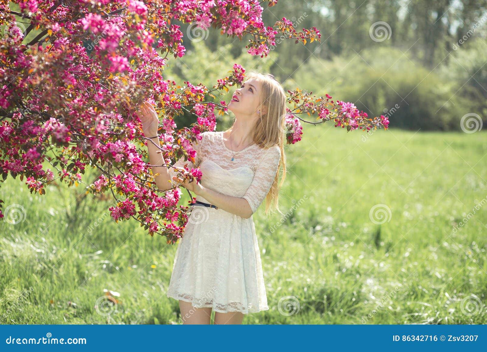 Moça bonita no vestido branco que aprecia o dia morno no parque durante a estação da flor de cerejeira em uma mola agradável