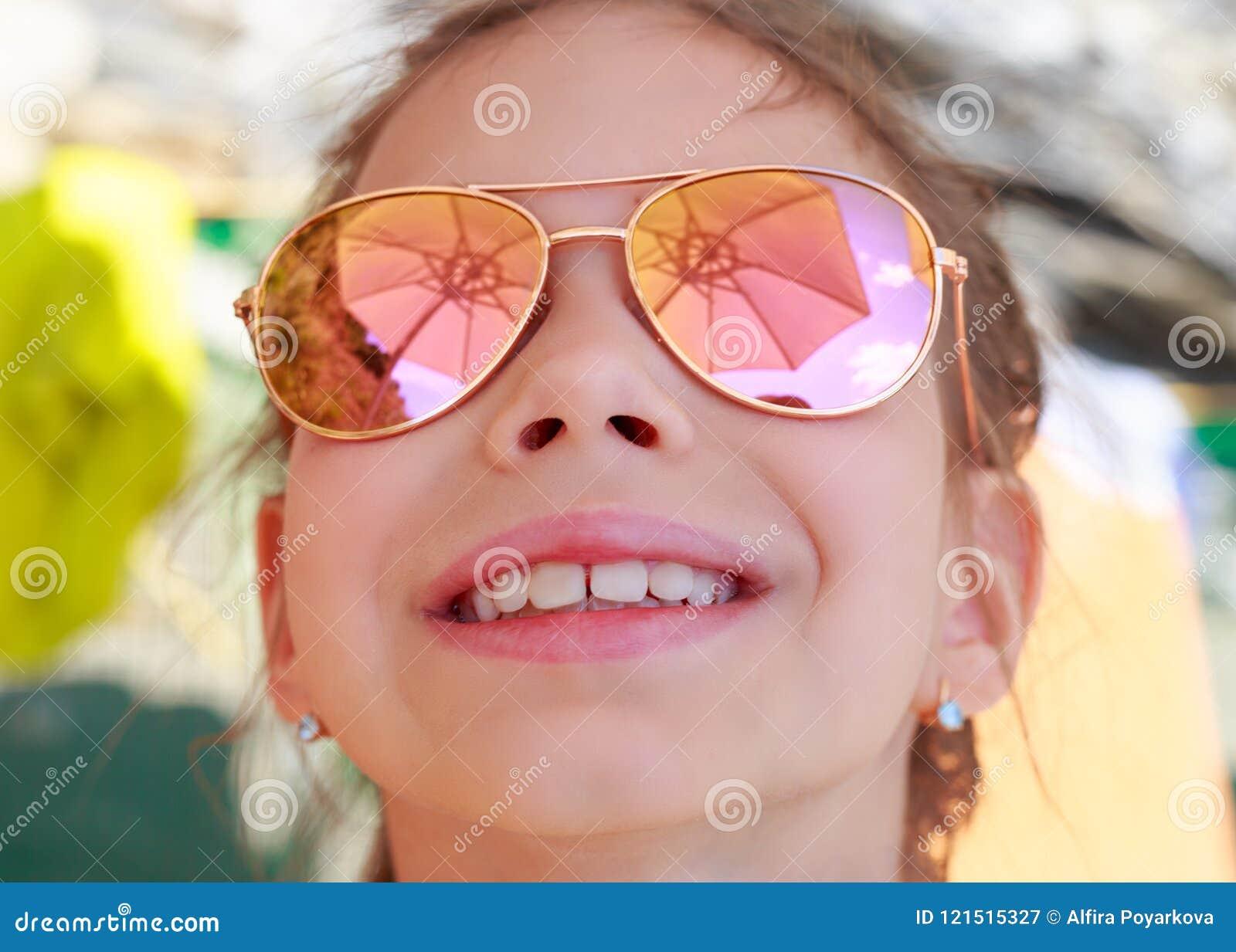 Moça bonita nos óculos de sol com reflexão do guarda-chuva de praia