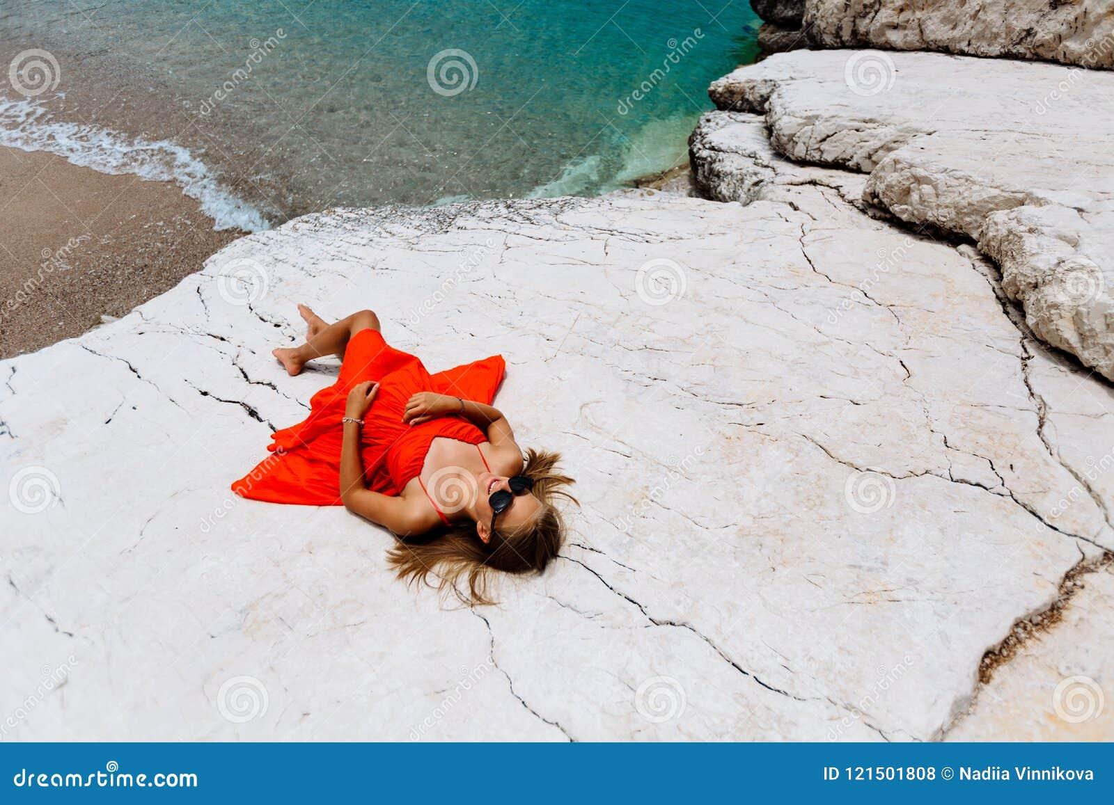 Moça bonita pelo mar Mulher em um vestido vermelho na praia Férias do beira-mar Terreno rochoso