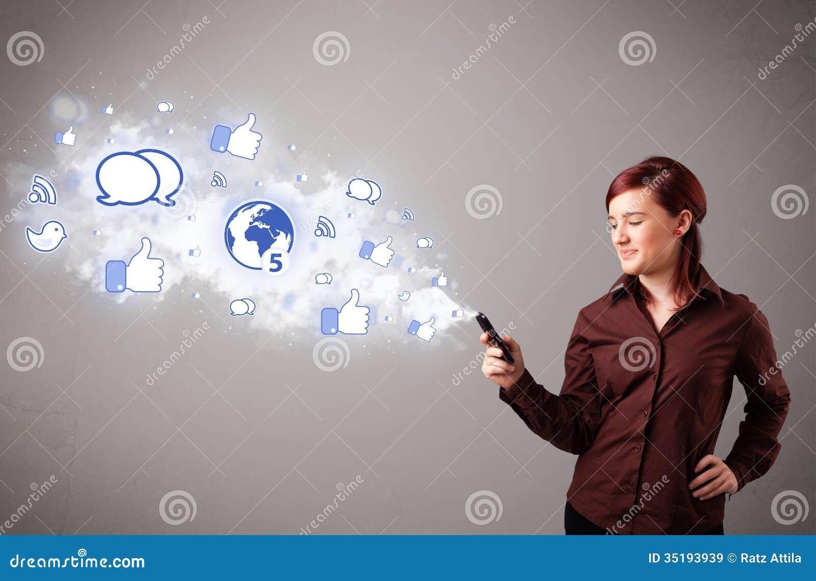 Moça bonita que guarda um telefone com ícones sociais dos meios