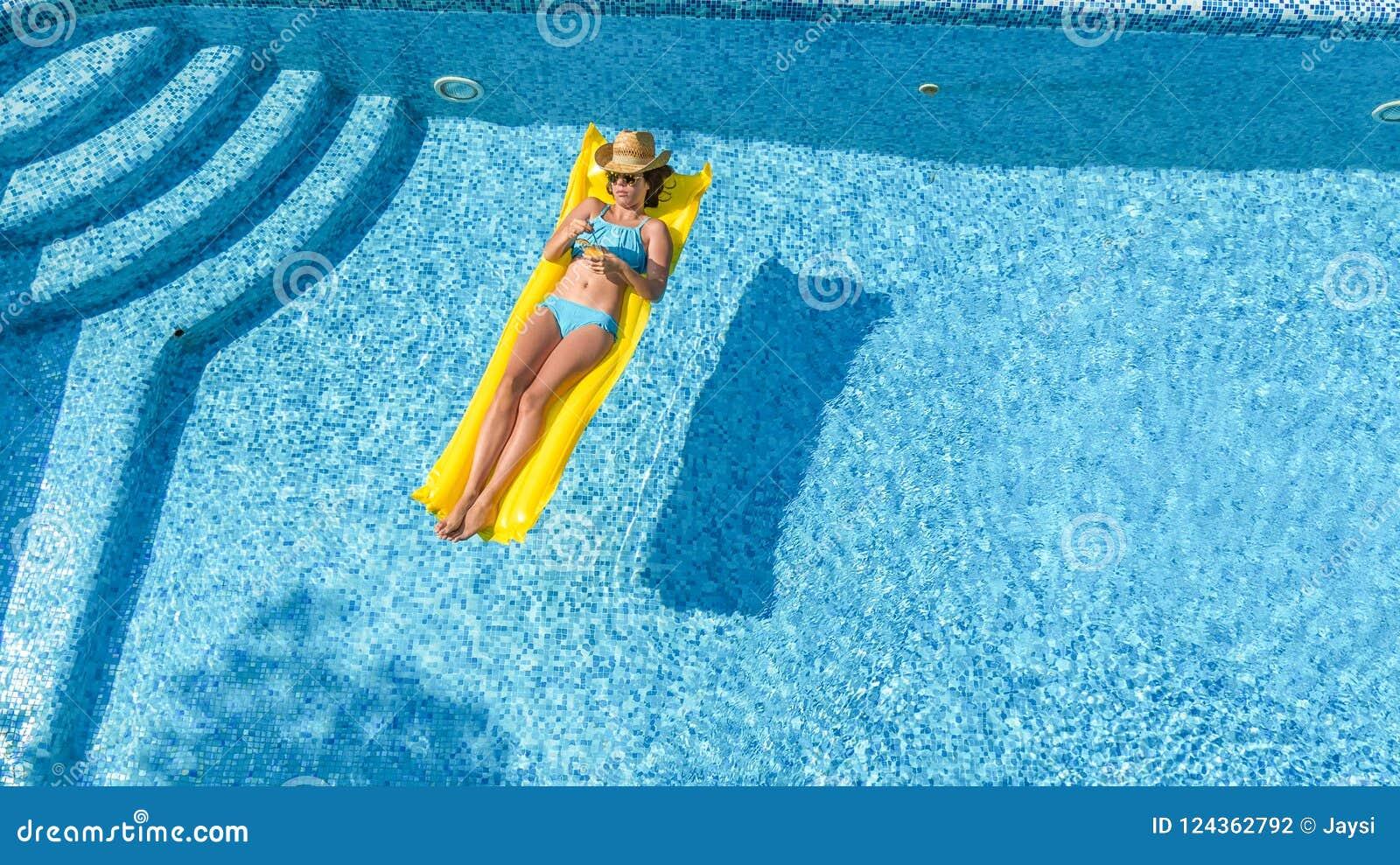 A moça bonita que relaxa na piscina, nadadas no colchão inflável e tem o divertimento na água em férias em família, vista aérea