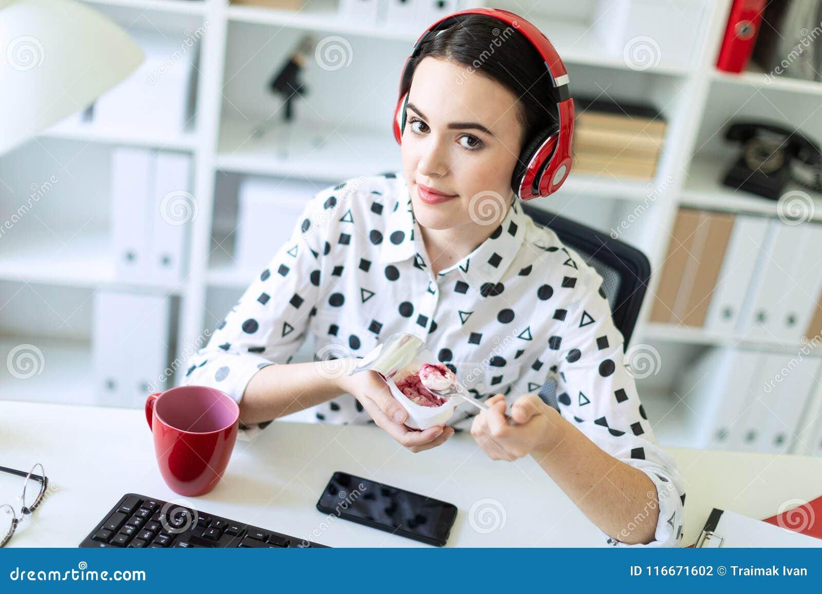 Moça bonita que senta-se nos fones de ouvido na mesa no iogurte comer do escritório com enchimento vermelho