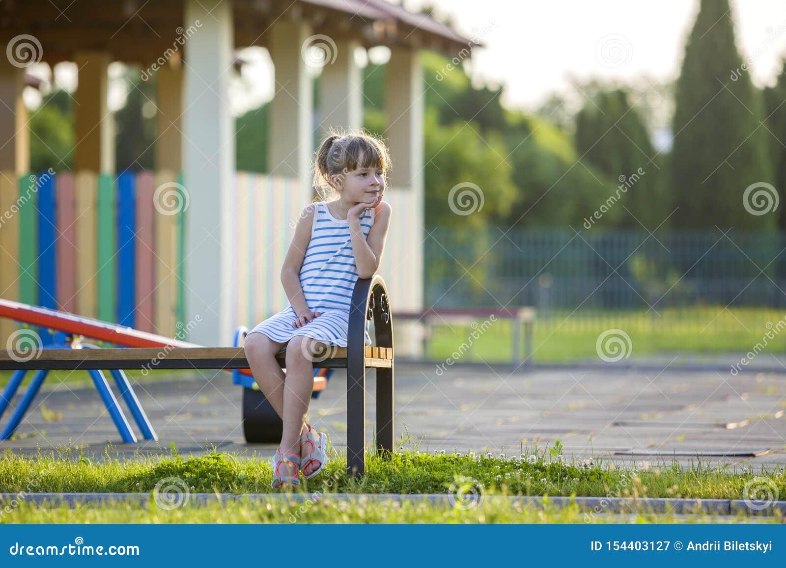 Moça bonito de sorriso que senta-se apenas fora no banco no dia de verão ensolarado