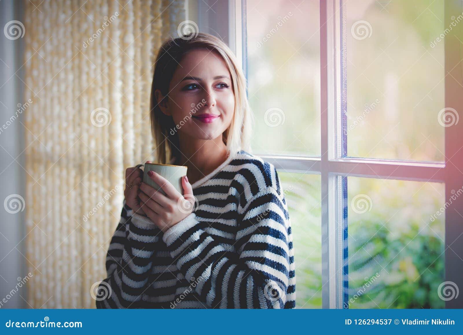 Moça com estada da xícara de café perto da janela