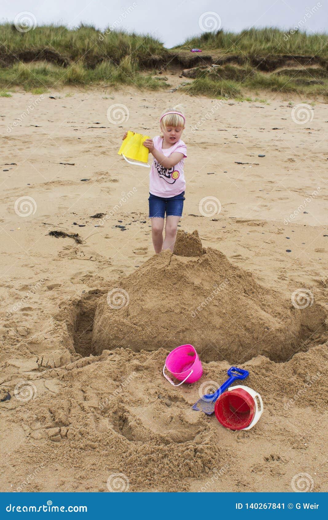A moça constrói um castelo da areia