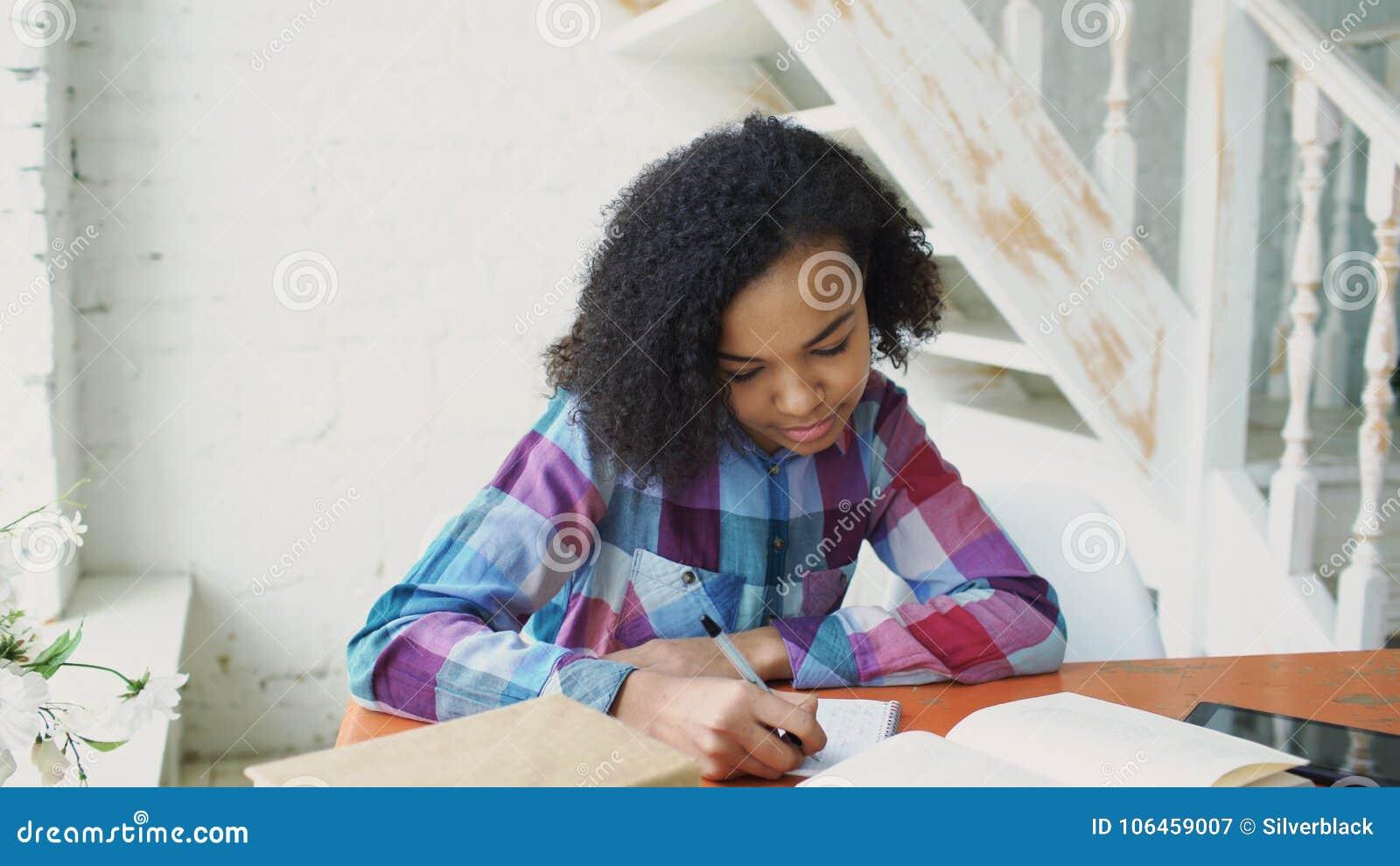 Moça de cabelo encaracolado adolescente da raça misturada que senta-se na concentração da tabela focalizada aprendendo lições par