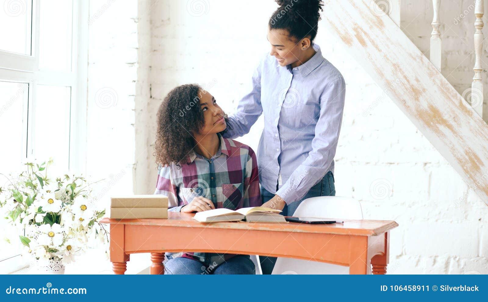 Moça de cabelo encaracolado adolescente da raça misturada que senta-se na concentração da tabela focalizada aprendendo lições e s